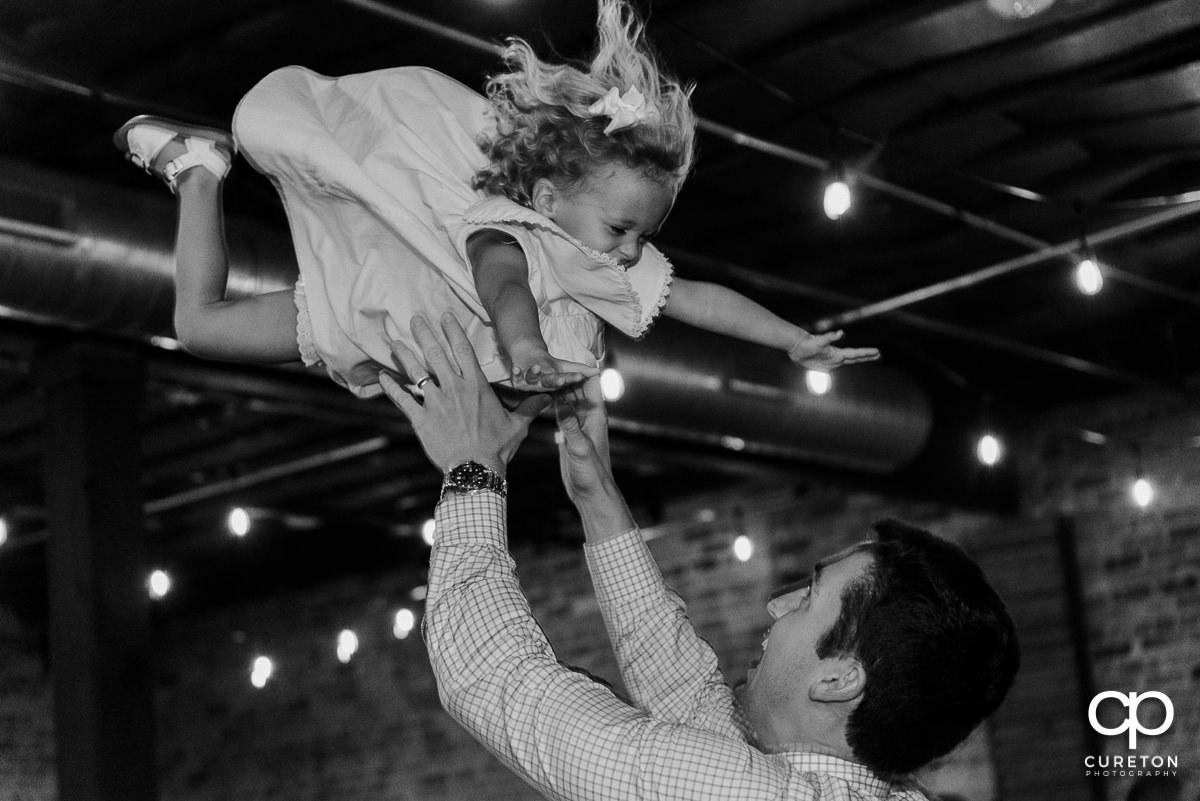 Man throwing his daughter in the air on the dance floor at the wedding.