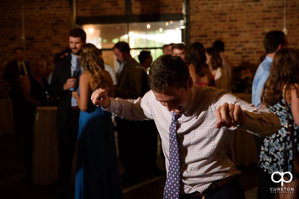 Man dancing at the reception.