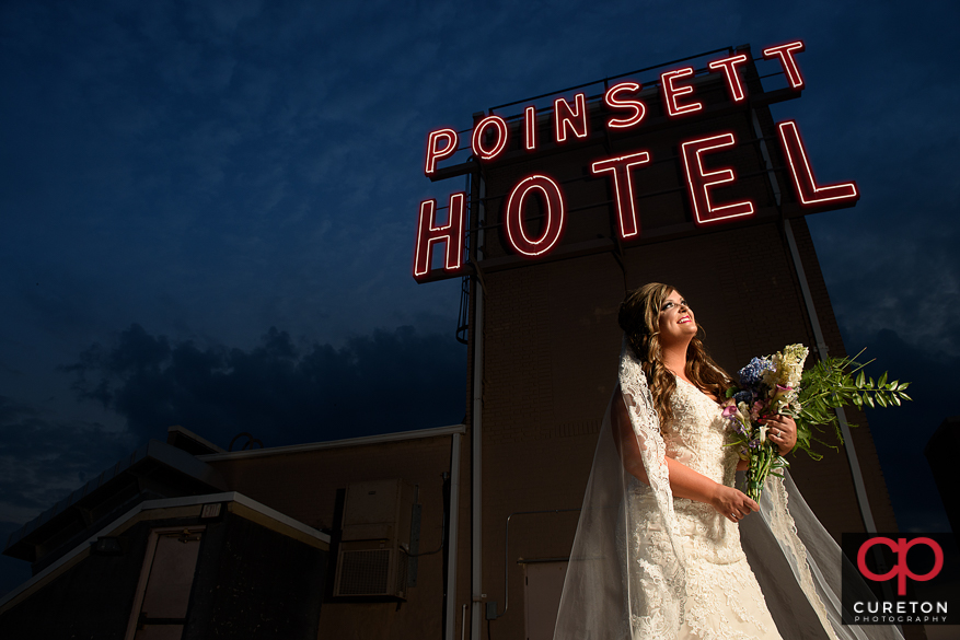 Bride on the roof of the Westin Poinsett near the sign during a pre wedding bridal session in Greenville,SC.