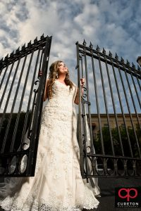 Bride holding onto an iron gate in downtown Greenville,SC during a bridal session.