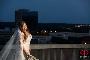 Bride at twilight on a rooftop overlooking the downtown Greenville,SC skyline.