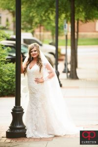 Bride leaning on a light pole in downtown Greenville,SC.