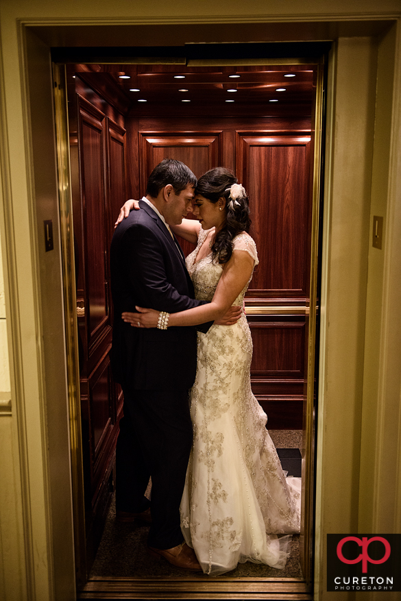 Bride and groom in the elevator at the Westin Poinsett hotel.