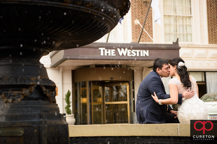 Married couple kissing by the fountain at the Westin in downtown Greenville,SC.