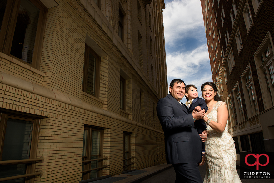 Bride and groom with their young son in downtown Greenville,SC at the Westin.