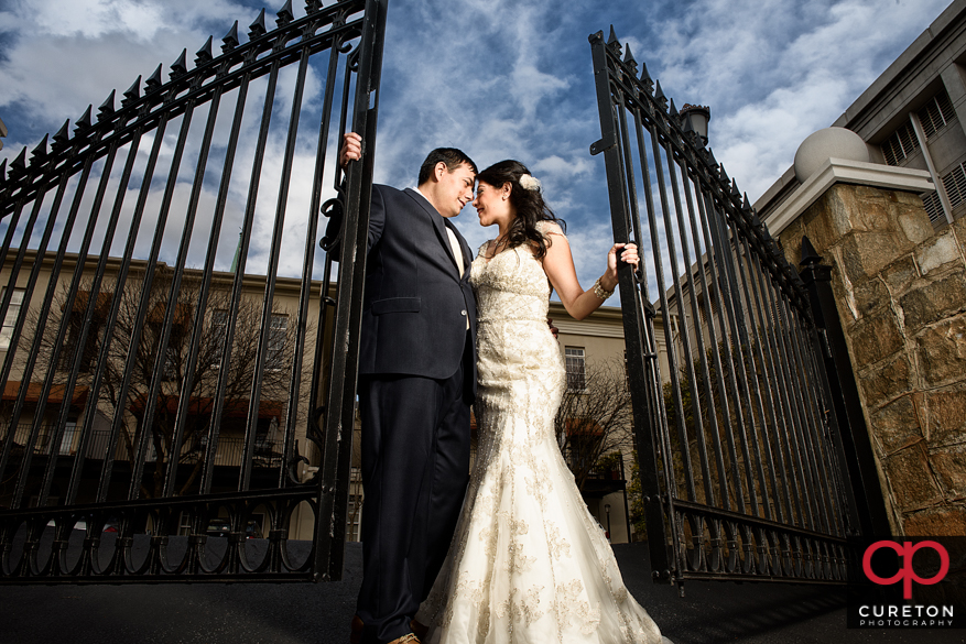Epic wedding portrait of bride and groom with an iron gate.