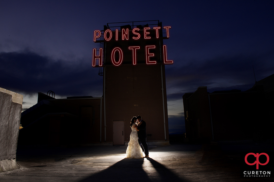 Iconic westin poinsett sign on the rooftop with bride and groom.