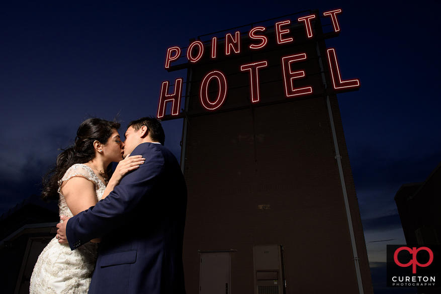Bride and groom with the iconic Westin Poinsett sign on the rooftop of the hotel.