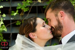Bride and groom kissing in downtown Greenville before their Westin Poinsett wedding.