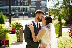 Bride and groom kissing on the streets of downtown Greenville.