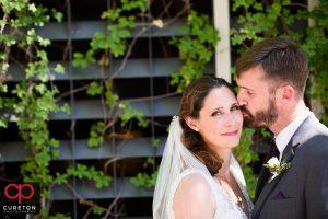 Groom kissing his bride on the cheek.