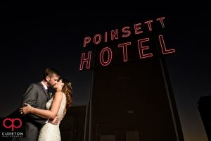 Epic shot of a bride and groom kissing near the sign on the Westin Poinsett rooftop during their wedding reception.