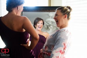 Bridesmaids laughing while getting ready.
