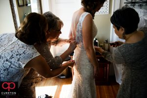Bridesmaids helping the bride into her dress.