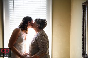 Bride's mom kissing the bride on the cheek.