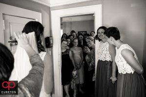 Bridesmaids watching as the bride is revealed.