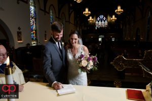 Bride and groom signing the marriage license at St. Mary's.