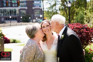 Brides parents both kissing her on the cheek after her wedding.