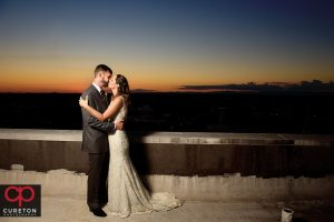 Bride and groom sharing a sunset on the roof.