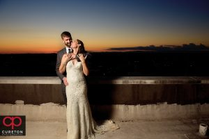 Bride and groom on the roof at sunset.