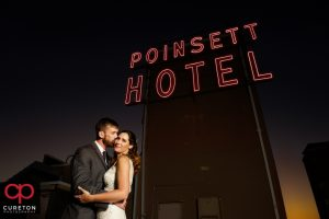 Bride and groom with the Westin Poinsett hotel sign.