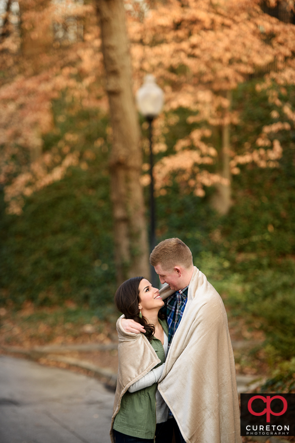 Couple cuddling during a winter falls park engagement session in Greenville,SC.
