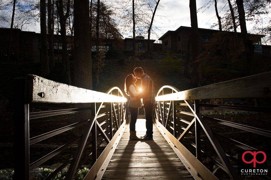 Couple kissing on a bridge during a winter falls park engagement session in Greenville,SC.