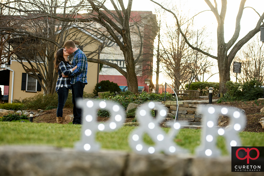 Engaged couple kissing behind a wedding sign.