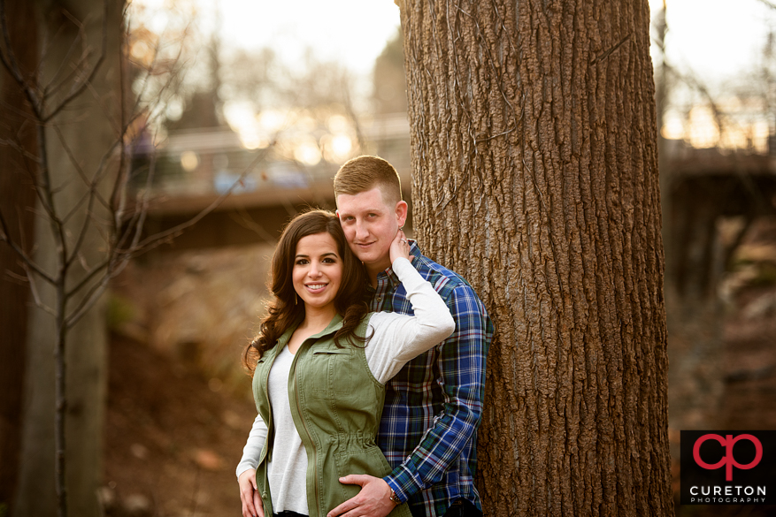 Couple leaning ona tree suring an engagement session infall spark.