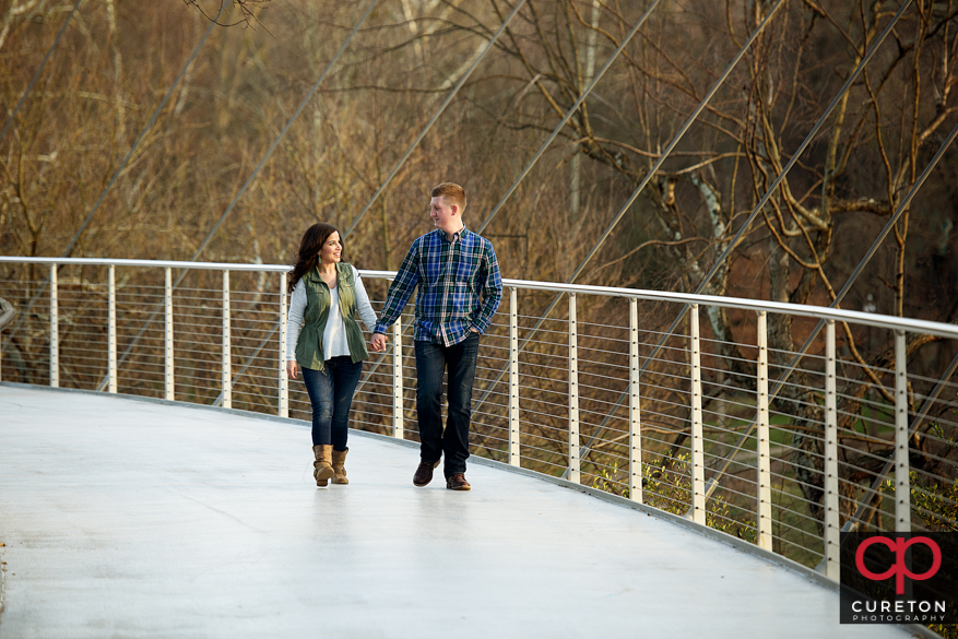 Engaged couple walking on Liberty Bridge.
