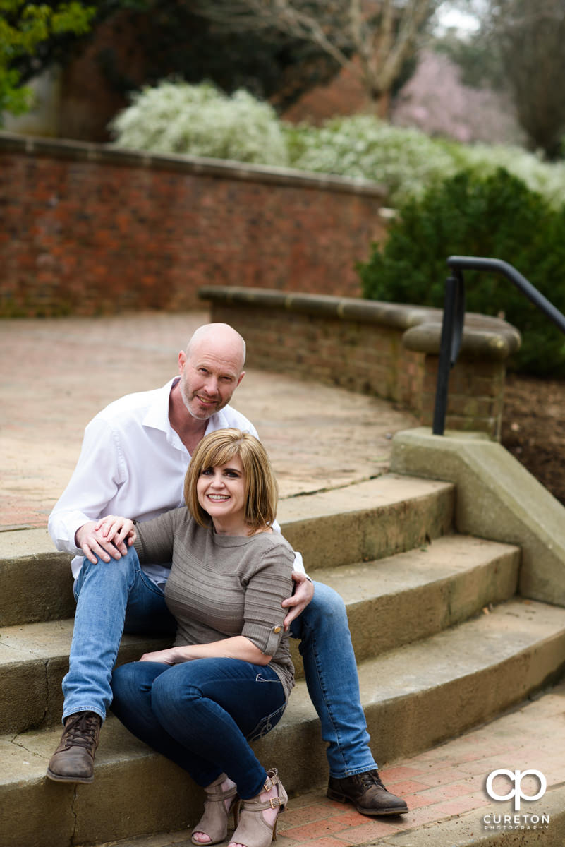 Engaged couple sitting on the steps outside the garden during a Furman University Engagement session in Greenville,SC.