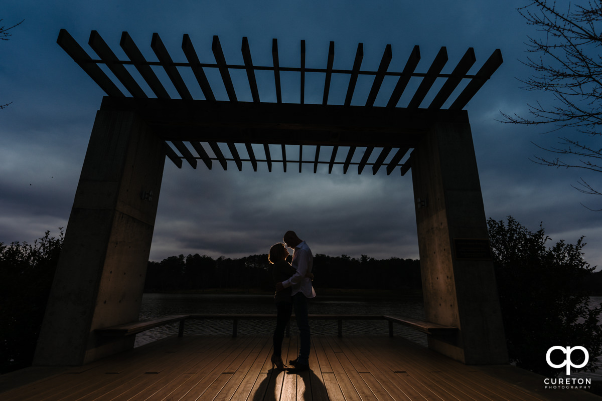Future bride and groom dancing at sunset by the lake during a Furman University winter Engagement session in Greenville,SC.