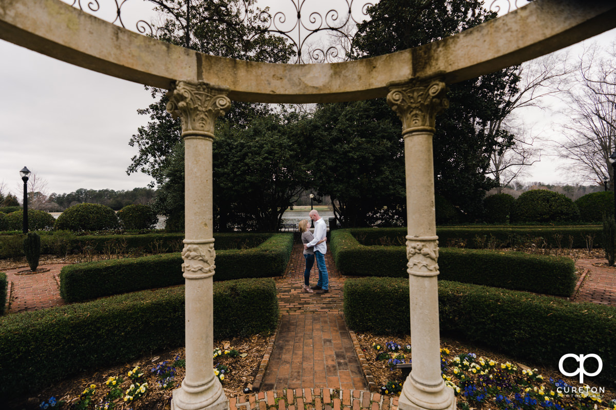 Future husband and wife standing in the middle of the rose garden during a Furman University winter Engagement session in Greenville,SC.