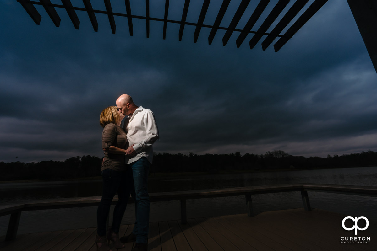 Man kissing his fiancee by the lake during a Furman University winter Engagement session in Greenville,SC.