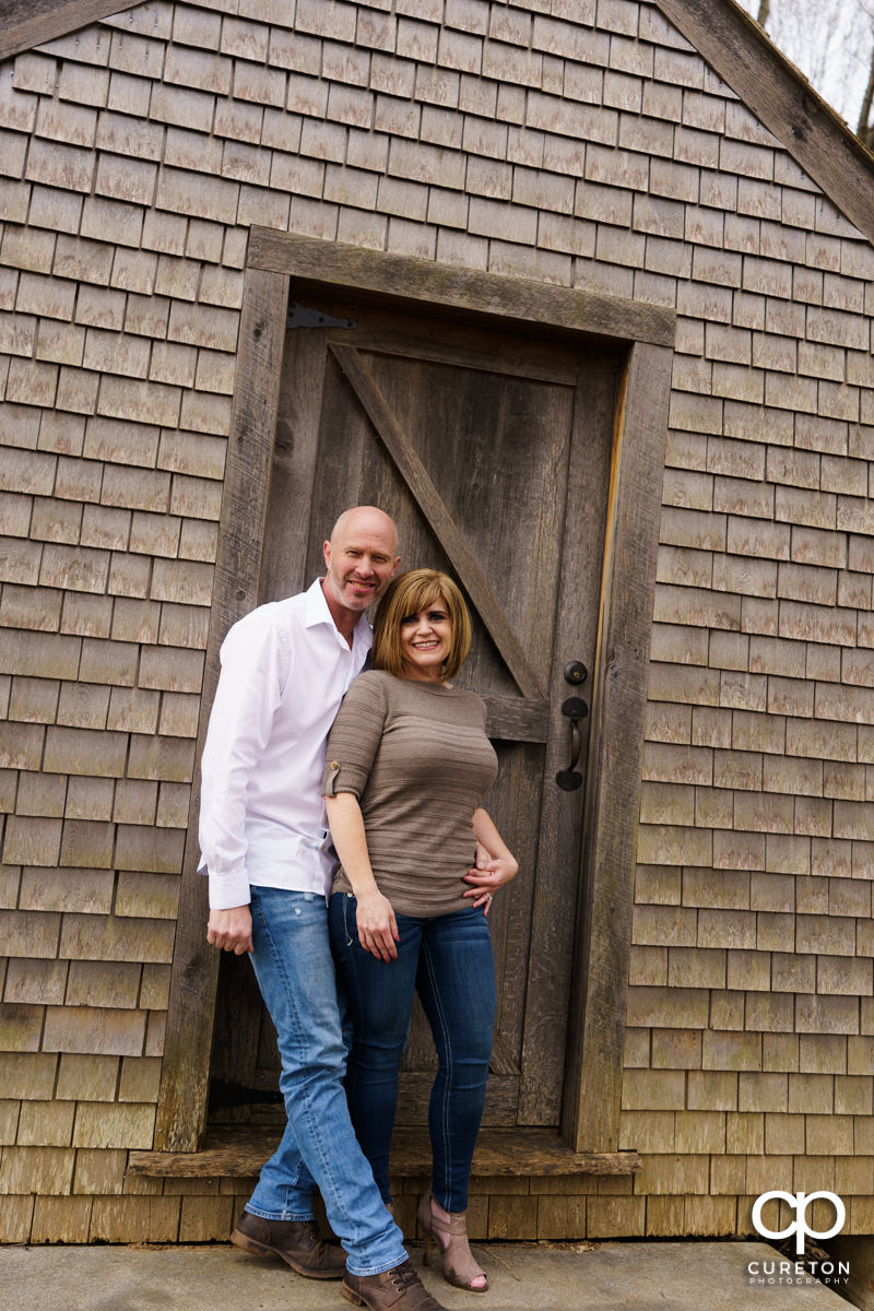 Man leaning on a rustic cabin with his fiancee.