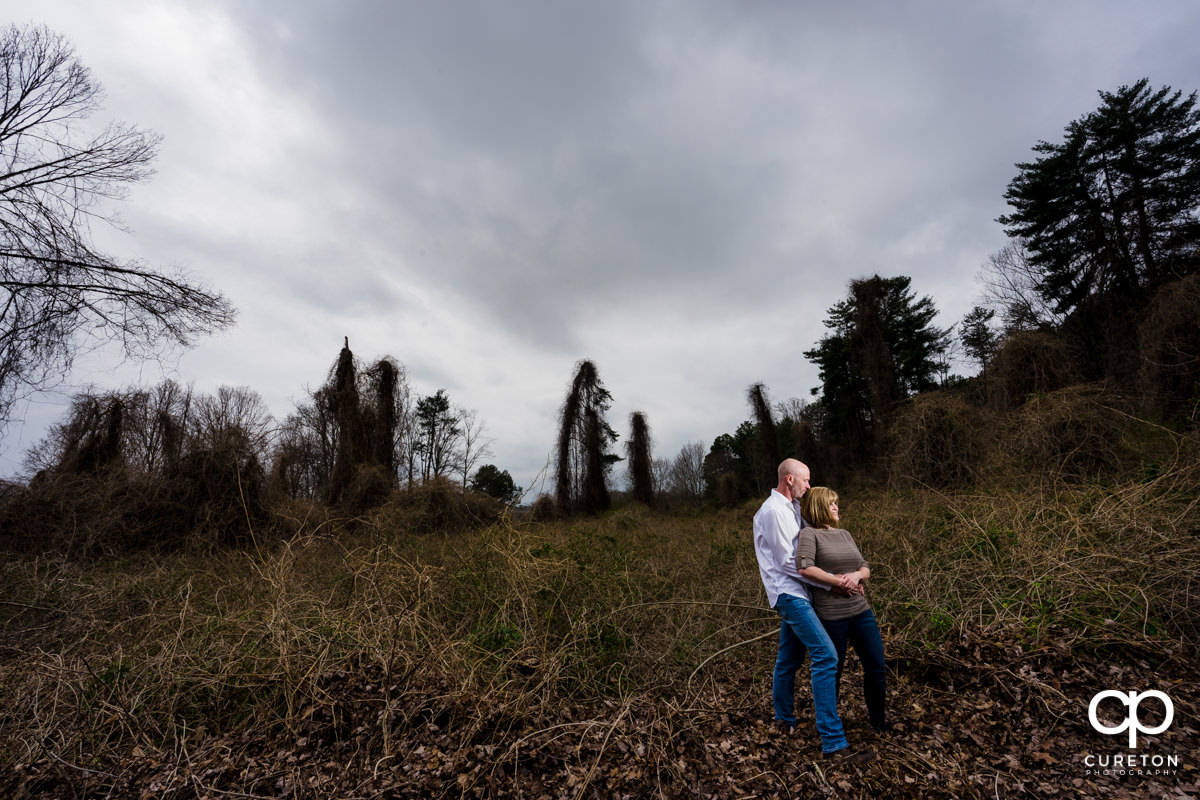 Future bride and groom standing in an overgrown field during a Furman University winter Engagement session in Greenville,SC.