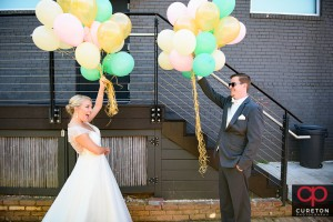 Creative first look at Zen with bride and groom holding balloons.