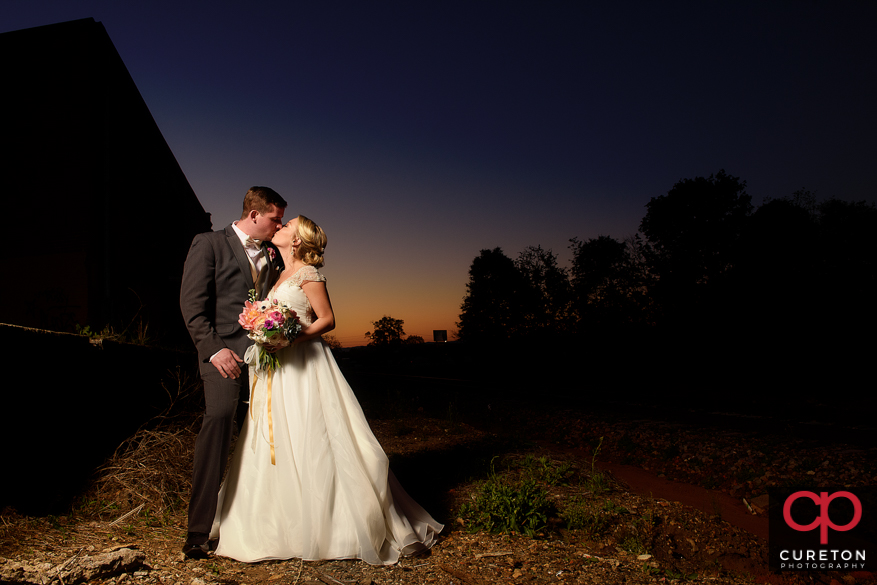 Bride and groom kissing at sunset after their Zen Greenville wedding.